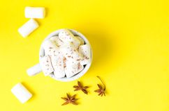 在一个咖啡杯的白色蛋白软糖在明亮的黄色背景 辣香料八角 库存图片