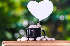 在一个咖啡杯的纸有在一个木板和Bokeh树背景的石头的 免版税图库摄影