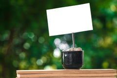 在一个咖啡杯的纸有在一个木板和Bokeh树背景的石头的 免版税库存图片