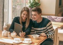 在一个咖啡馆的快乐的夫妇约会与片剂 免版税库存照片