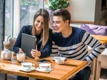 在一个咖啡馆的快乐的夫妇约会与片剂 免版税库存图片