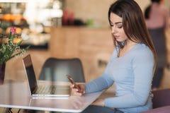 在一个咖啡馆的美丽的深色的女商人用途电话与膝上型计算机 免版税库存图片