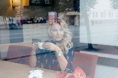 在一个咖啡馆里面的美丽的女孩与咖啡 库存图片
