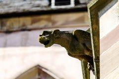 在一个哥特式大教堂的面貌古怪的人,一个塔的细节在蓝天ba的 库存图片