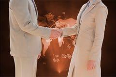 在一个商人和一名女实业家之间的握手反对全世界地图背景 免版税库存图片