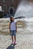 在一个喷泉前面的一个女孩在弗罗茨瓦夫,波兰中央集市广场  免版税图库摄影