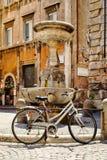 在一个喷泉旁边的老自行车在一个小正方形在中央罗马 免版税库存图片