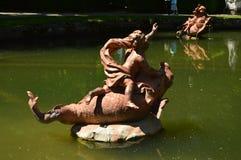 在一个喷泉的雕塑有小的天使的在农场的庭院里发出水的鱼顶部 艺术史生物 免版税库存照片