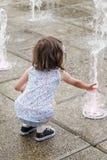 在一个喷泉耽溺于在一个热的夏日的女孩 免版税库存照片