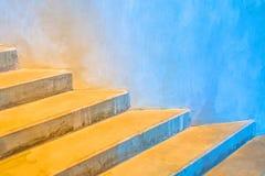 在一个圆的大厦附近的具体台阶与从温暖的黄色的一个颜色梯度到冷的蓝色 免版税库存图片