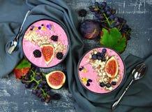 在一个圆的碗的圆滑的人用无花果、黑莓和葡萄 库存照片