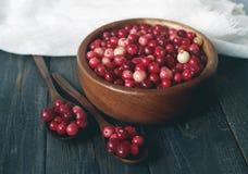 在一个圆的碗的新鲜的红色森林蔓越桔有在白色亚麻制织品的一把木匙子的桌表面上 免版税库存图片