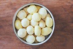 在一个圆的碗的未加工的被剥皮的土豆在一个老土气木桌特写镜头 免版税库存照片