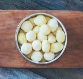 在一个圆的碗的未加工的被剥皮的土豆在土气木桌特写镜头的一个老切板 免版税库存照片