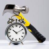 在一个圆的闹钟的概念性锤子工具 库存照片