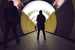 在一个圆隧道前面的剪影步行者和骑自行车者的 免版税图库摄影