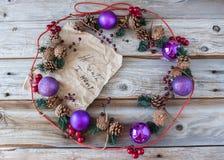 在一个圈子框架的紫色圣诞节球和杉木锥体在老土气木背景 免版税库存照片