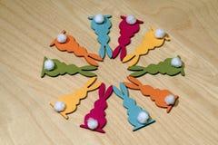 在一个圈子的十只五颜六色的木复活节兔子在木地下 免版税库存照片