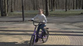 在一个圈子的女孩骑马在一辆淡紫色自行车在白色衣裳的春天公园在日落 城市公园 4K 25 fps 股票录像