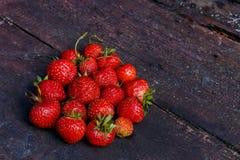 在一个圈子的形状的草莓在颜色木背景的 图库摄影
