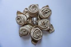 在一个圈子的金黄餐巾玫瑰与银色金属敲响中间装饰桌事件假日和党白色backgro 库存照片
