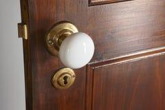 在一个土气传统木门的白色门把手 库存图片