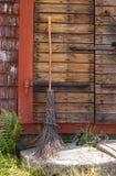 在一个土气房子的入口的笤帚 免版税库存照片
