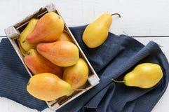 在一个土气木果子箱子的大水多的黄色梨在一张白色桌上 免版税库存图片