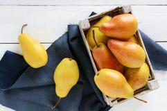 在一个土气木果子箱子的大水多的黄色梨在一张白色桌上 免版税库存照片