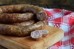 在一个土气样式的传统熏制的香肠圆环 开胃香肠由猪肉和羊羔制成用新鲜的草本,香料在woode 库存图片
