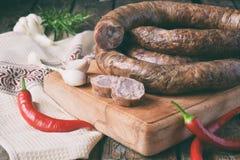在一个土气样式的传统熏制的香肠圆环 开胃香肠由猪肉和羊羔制成用新鲜的草本,香料在woode 图库摄影