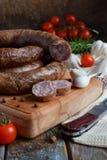 在一个土气样式的传统熏制的香肠圆环 开胃香肠由猪肉和羊羔制成用新鲜的草本,香料在woode 免版税图库摄影