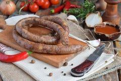 在一个土气样式的传统熏制的香肠圆环 开胃香肠由猪肉和羊羔制成用新鲜的草本,香料在woode 免版税库存图片