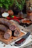 在一个土气样式的传统熏制的香肠 开胃香肠由猪肉和羊羔制成用新鲜的草本,香料在木蟒蛇 免版税库存图片