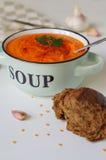 在一个土气碗的扁豆奶油色汤有黑面包片断的  免版税库存照片