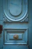 在一个土气蓝色门的黄铜门把手 免版税库存照片