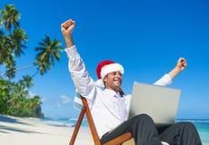 在一个圣诞老人帽子的一个商人在海滩 库存照片