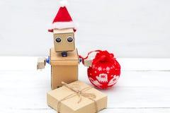 在一个圣诞老人帽子的机器人有礼物盒的 图库摄影