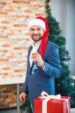 在一个圣诞老人盖帽的英俊的商人有在欢乐背景的一块玻璃的 企业圣诞晚会概念 免版税库存照片