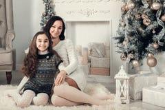 在一个地板上的两个俏丽的女孩、母亲和女儿选址在克里斯 图库摄影