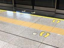 在一个地板上的前门脚印在地铁站乐团平台 免版税库存图片