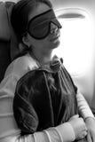 在一个地毯下的女孩与在她的眼睛的一个面具睡着在飞机上 免版税图库摄影