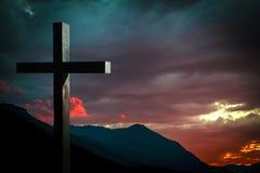 在一个场面的耶稣基督木十字架与剧烈的天空和五颜六色的日落,日出 免版税图库摄影
