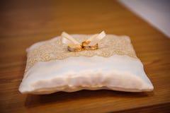 在一个坐垫的两只婚姻的金戒指圆环的 免版税库存照片