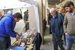 在一个块菌供营商前面的游人蒙卡尔沃,意大利块菌市场的  图库摄影