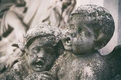 在一个坟茔的小的天使雕塑在坟园 与选择聚焦的被定调子的图象 免版税库存照片
