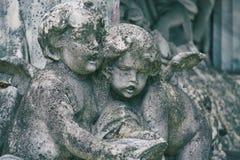 在一个坟茔的小的天使雕塑在坟园 被定调子的图象 免版税库存图片