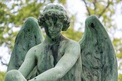在一个坟茔的年轻天使雕塑在坟园 库存照片
