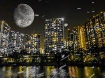 在一个城市的明亮的月亮由有轻微的雪的河 免版税库存图片