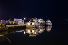 在一个城市码头的偏僻的老船在晚上 免版税库存图片